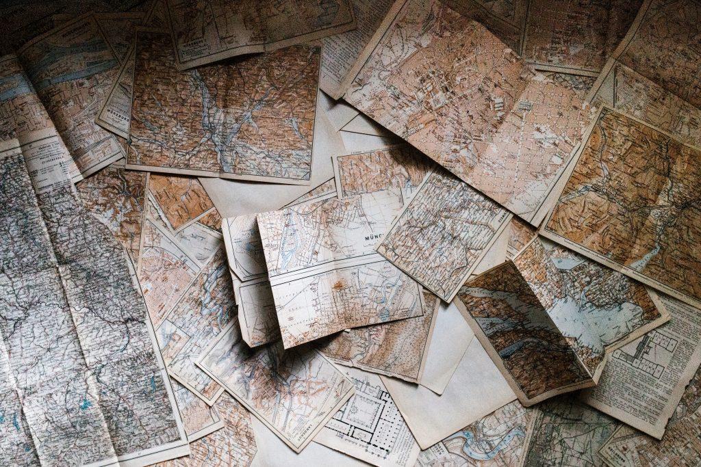 Diversos mapas abertos um em cima do outro vistos de cima