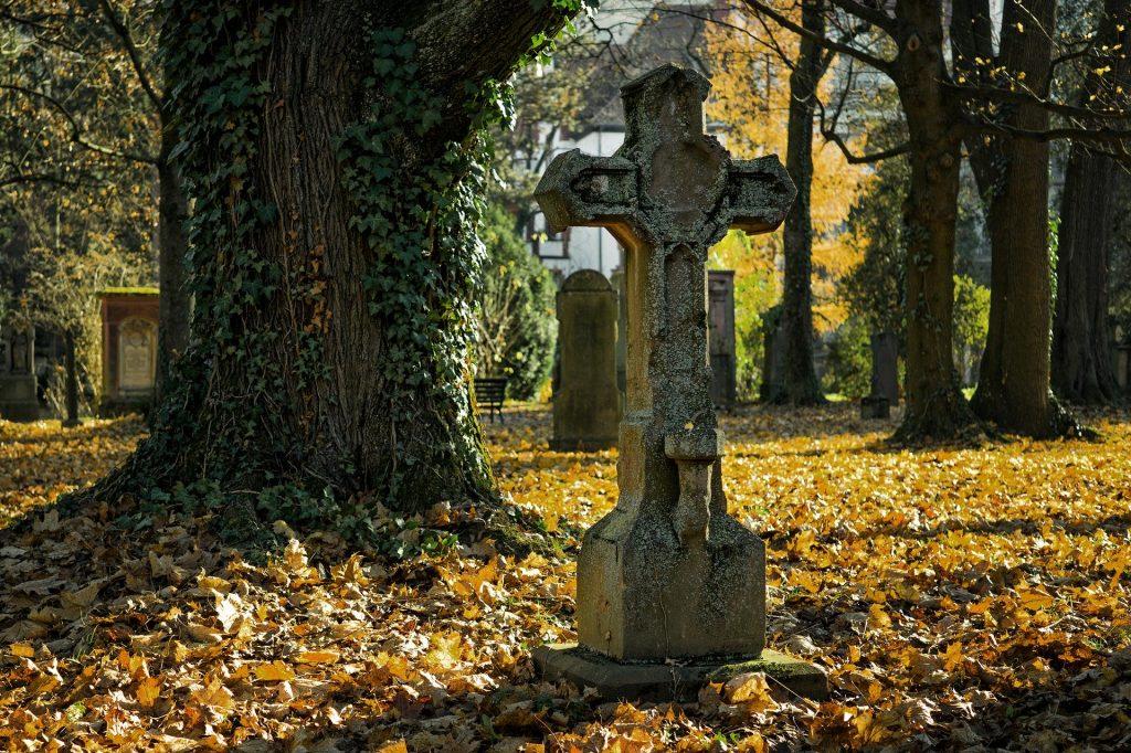 Imagem de uma cruz de cimento dentro de um cemitério. O chão está coberto de folhas da estação de outono.