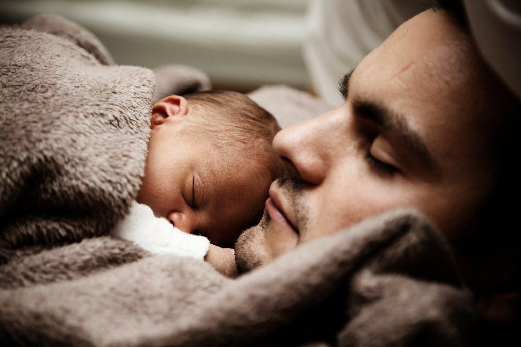 Homem deitado com os olhos fechados e dormindo. Sobre o colo dele está uma criança recém-nascida dormindo. Ambos estão cobertos com um coberta bege de pelo.