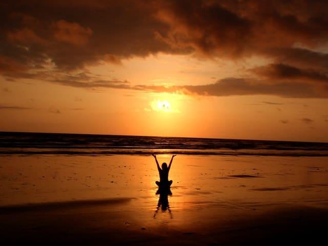 Silhueta de mulher sentada na praia com braços para o alto e sol e mar ao fundo