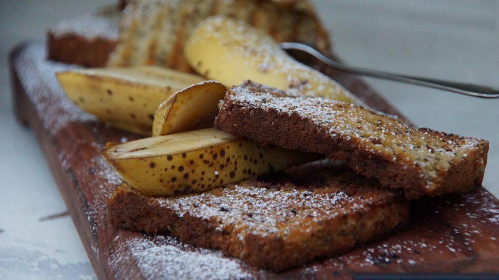 Bolo de banana já assado. Sobre ele fatias de banadas cortadas no comprimento cobertas com açúcar e canela.
