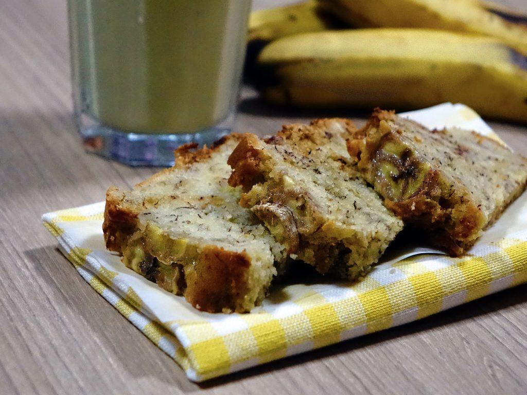 Três fatias de bolo de banana colocadas sobre uma toalha xadrez nas cores amarelo e branco, Ao lado bananas inteira e um copo de suco de banana.