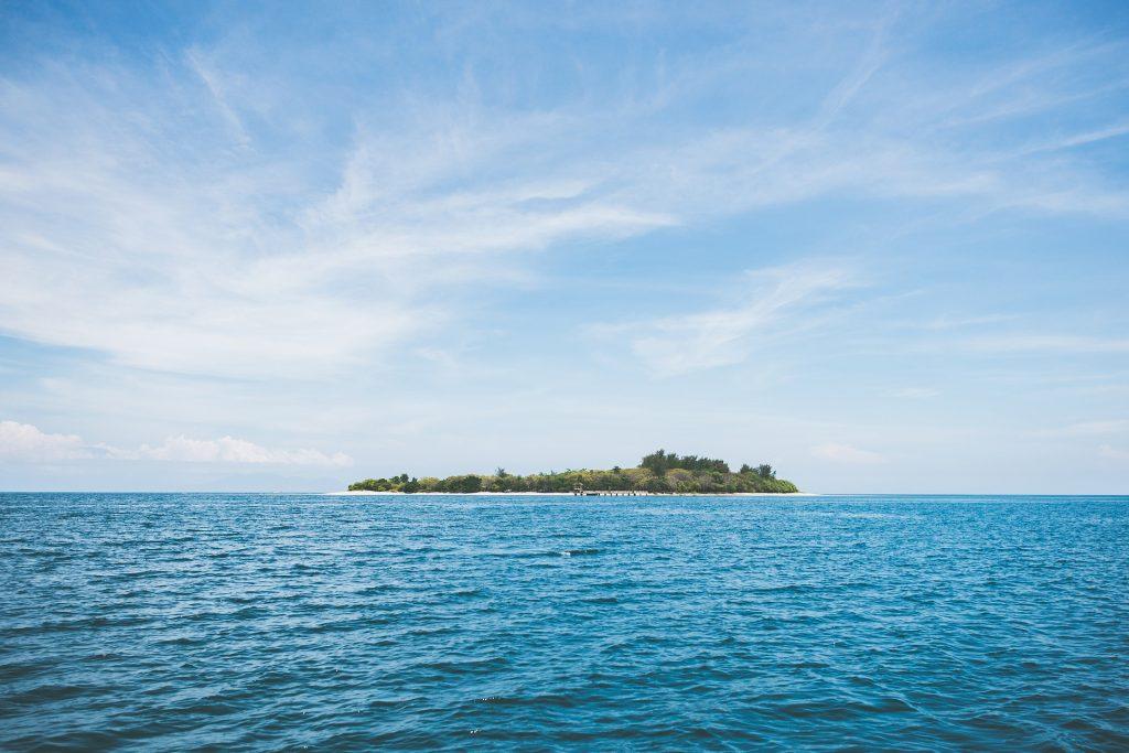 Imagem de uma praia bem azul. Ao fundo uma ilha extensa.