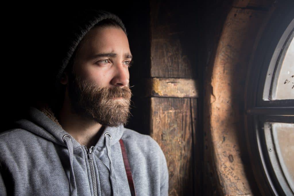 Imagem de um homem olhando para uma janela de madeira. Ele tem barba e bigode. Usa uma touca de lã e um moletom cinza. Seu olhar é de tristeza.