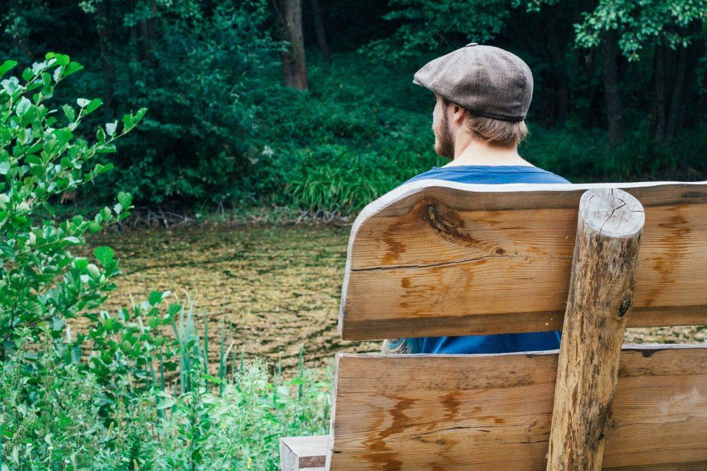 Homem jovem usando barba e boina sentando em um banco de madeira no meio de uma floresta. Ele está em silêncio contemplando a beleza da natureza.