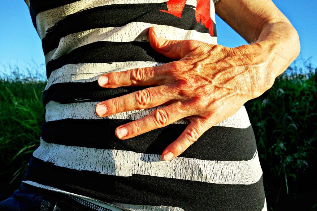 Imagem de uma mão de uma senhora sobre o seu estômago. Ela veste uma blusa listrada nas cores preto e cinza.