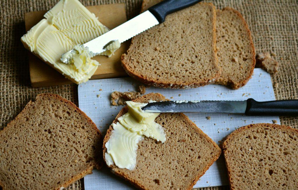 Várias fatias de pão de forma integral. Um deles está com manteiga.