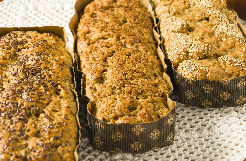 Três formas retangulares de papelão contendo cada uma delas um pão integral de sabor diferenciado.