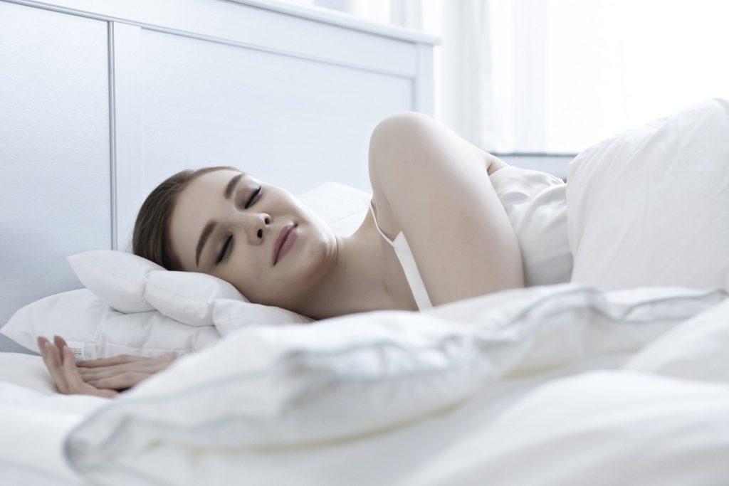 Imagem de uma mulher dormindo em um quarto todo branco. Ela dorme tranquila e em paz.