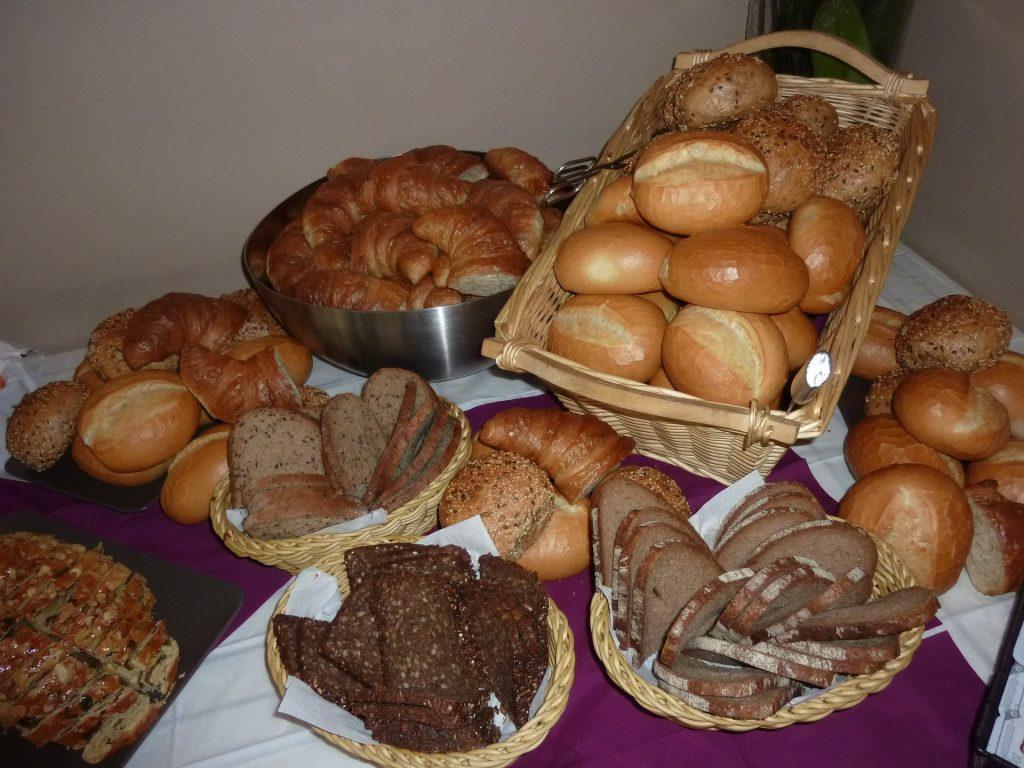 Diversos cestos com variados tipos de pães inntegrais. Os cestos estão distribuídos sobre uma mesa com uma toalha lilás e branca.