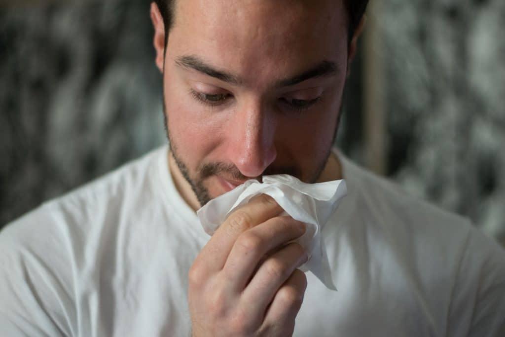 Homem limpando nariz com papel.