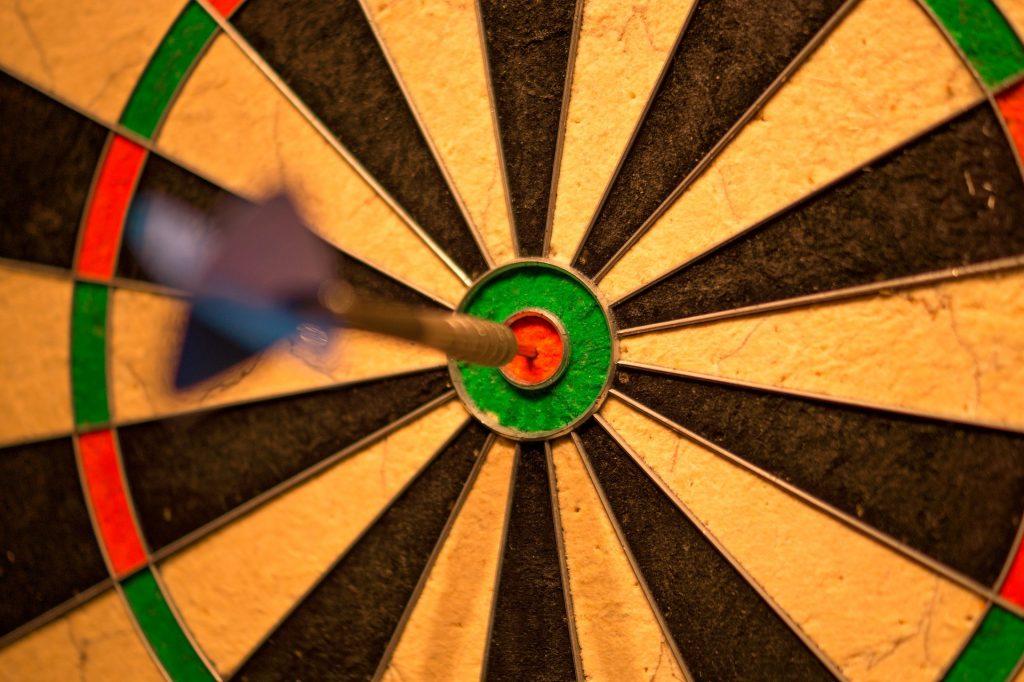 Tábua de tiro ao alvo com uma flecha direcionada no alvo.