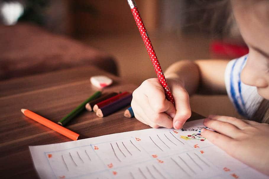 Menina desenhando e escrevendo com lápis em um papel.