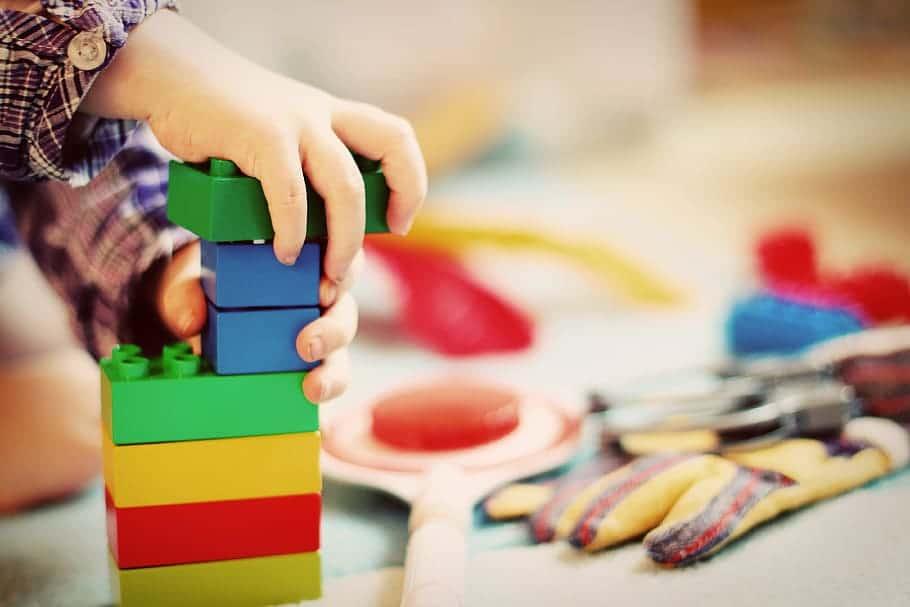 Mão de criança montando torre com peças de blocos de brinquedo.