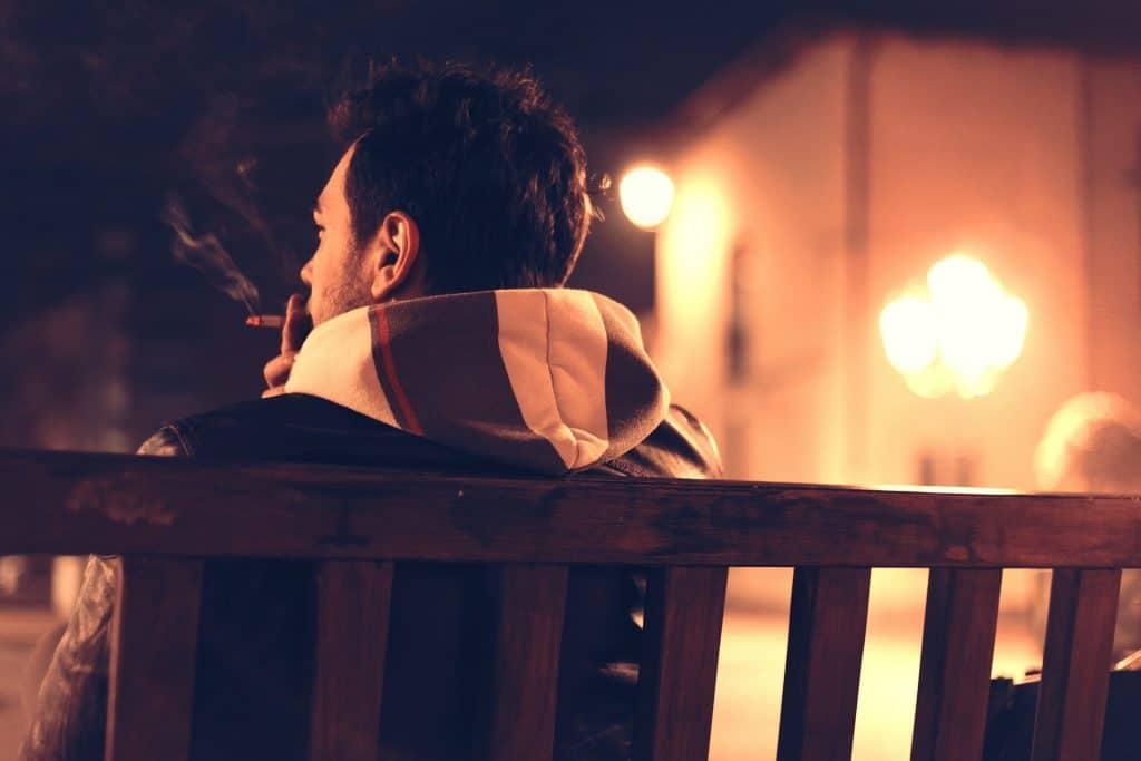 Imagem de um homem jovem, agasalhado com um blusa de moletom com touca. Ele está sentando em um banco de um praça fumando um cigarro.