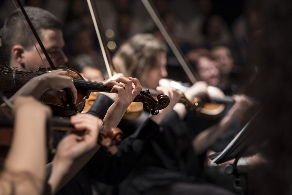 Imagem de músicos tocando violino em uma apresentação de música clássica.