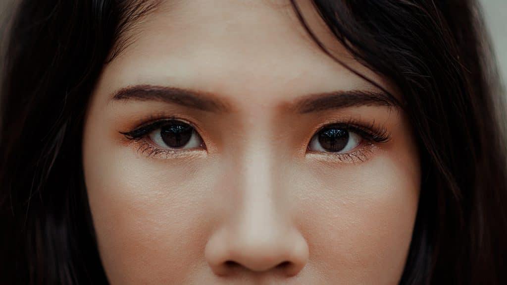 Foto em close-up dos olhos de uma menina com traços sino-asiáticos.