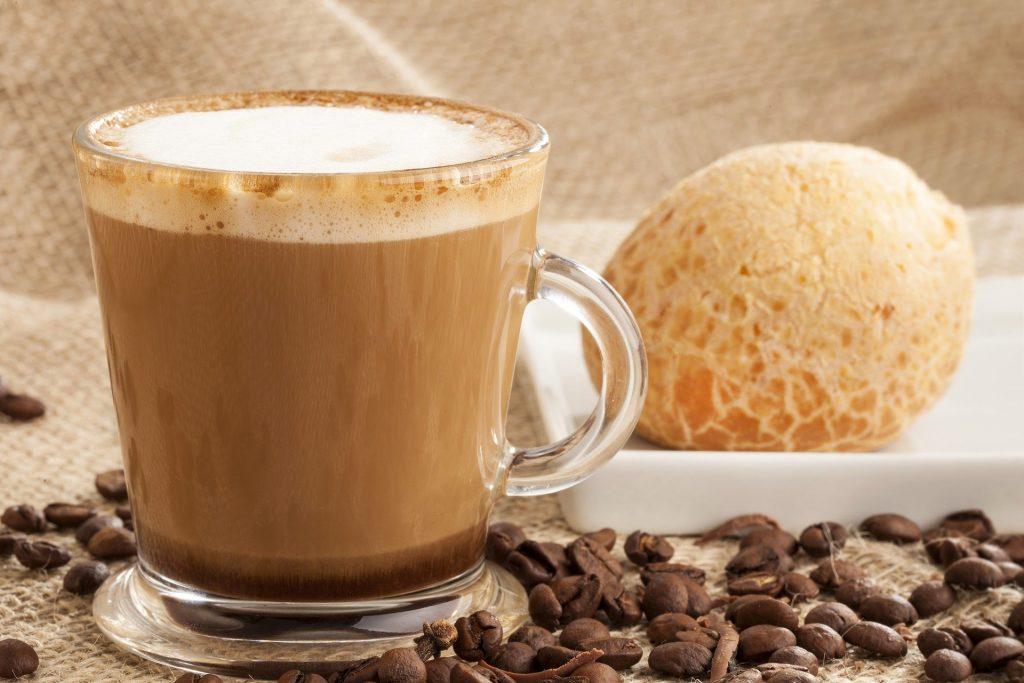 Xícara de vidro com café com leite. Ao lado um pão de queijo dispostos sobre uma mesa decorada com um pano de juta e grãos de café.