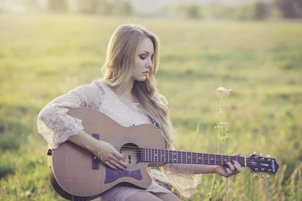 Imagem de uma mulher loura sentada em um gramado. Ela usa um vestidode renda bege claro e segura em suas mãos um violão,