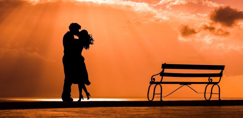 Imagem de um casal homem e mulher. Eles estão se beijando em frente ao mar em um lindo por do sol. Ao lado um banco de ferro compõe a imagem.