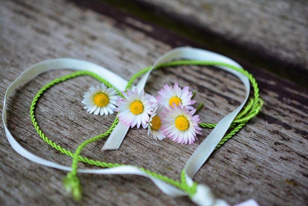 Imagem de um coração desenhado com fita e barbante fino nas cores verde escura e verde claro. Ao centro algumas flores de margaridas brancas.