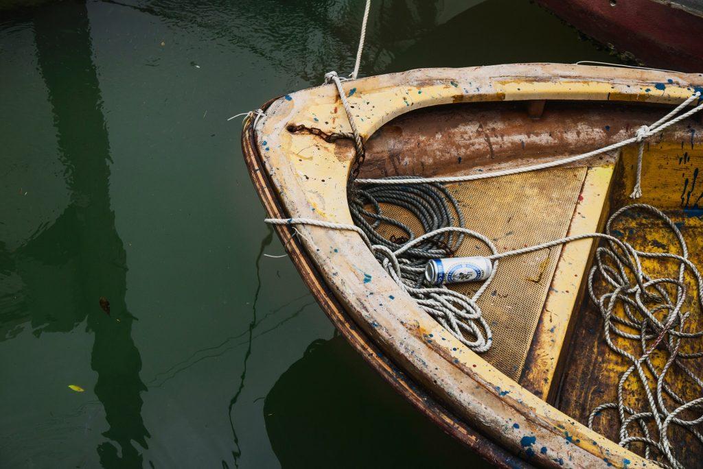 Água suja e ao lado um bote velho com cordas e uma lata de alumínio de bebida.