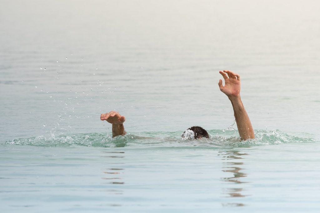 Imagem de um homem se afogando em um rio. Ele está com os braços levantados e a cabeça embaixo da água.