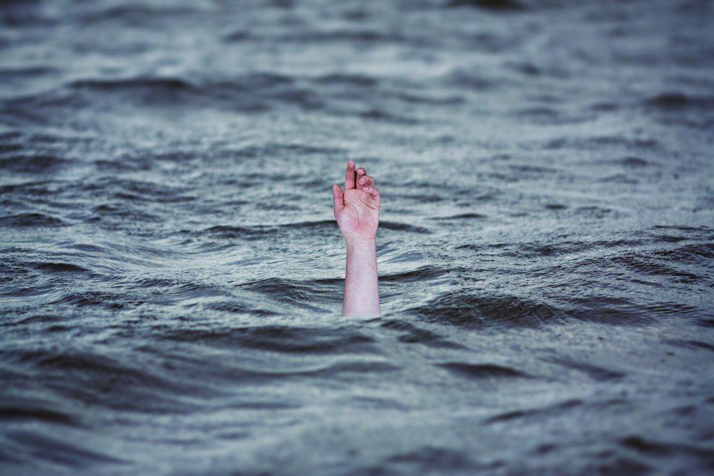 Cena de uma mão de uma pessoa se afogando em alto mar.