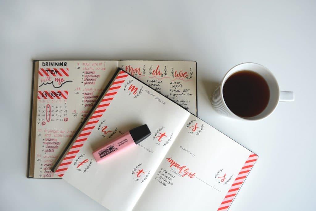 Mesa vista de cima com cadernos de planejamento e xícara de chá