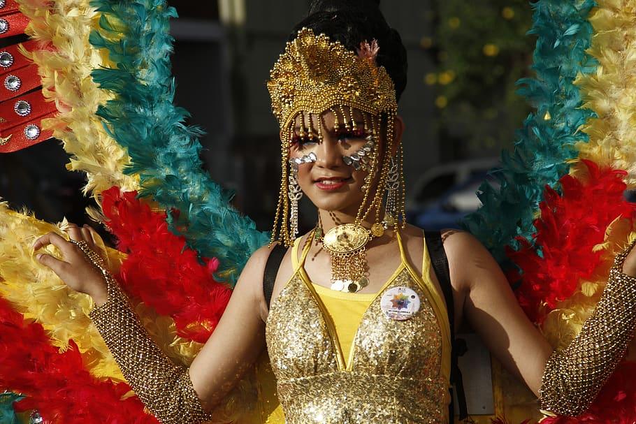 Mulher com fantasia de carnaval dourada, com coroa cheia de pedras douradas e prateadas penduradas, e asas grandes com penas em azul, vermelho e amarelo pendurada em suas costas.