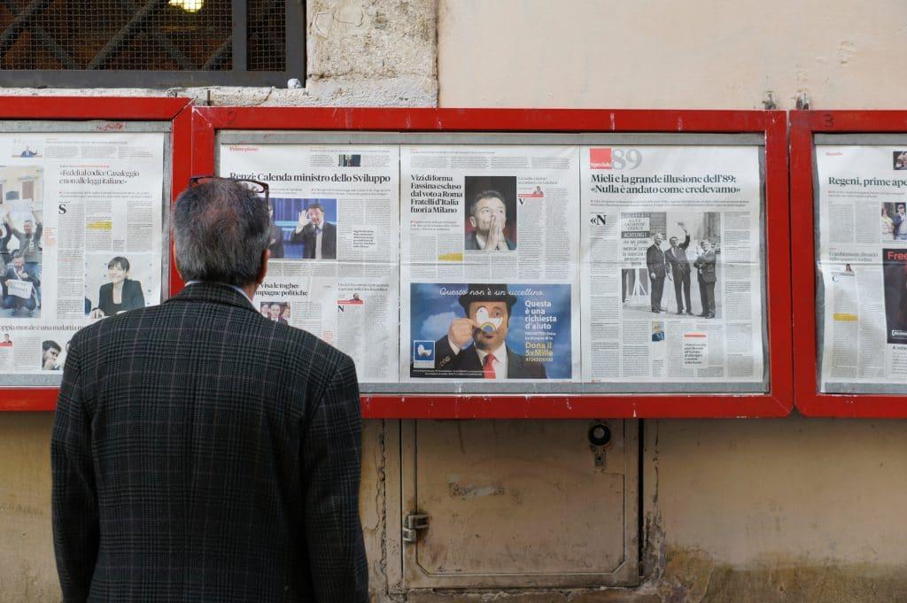 Homem idoso de costas, vestindo um paletó e com óculos sobre a cabeça, olha para um mural de notícias na rua.