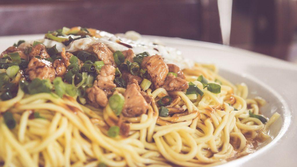 Prato de macarrão espaguetti com frango em pedaços.