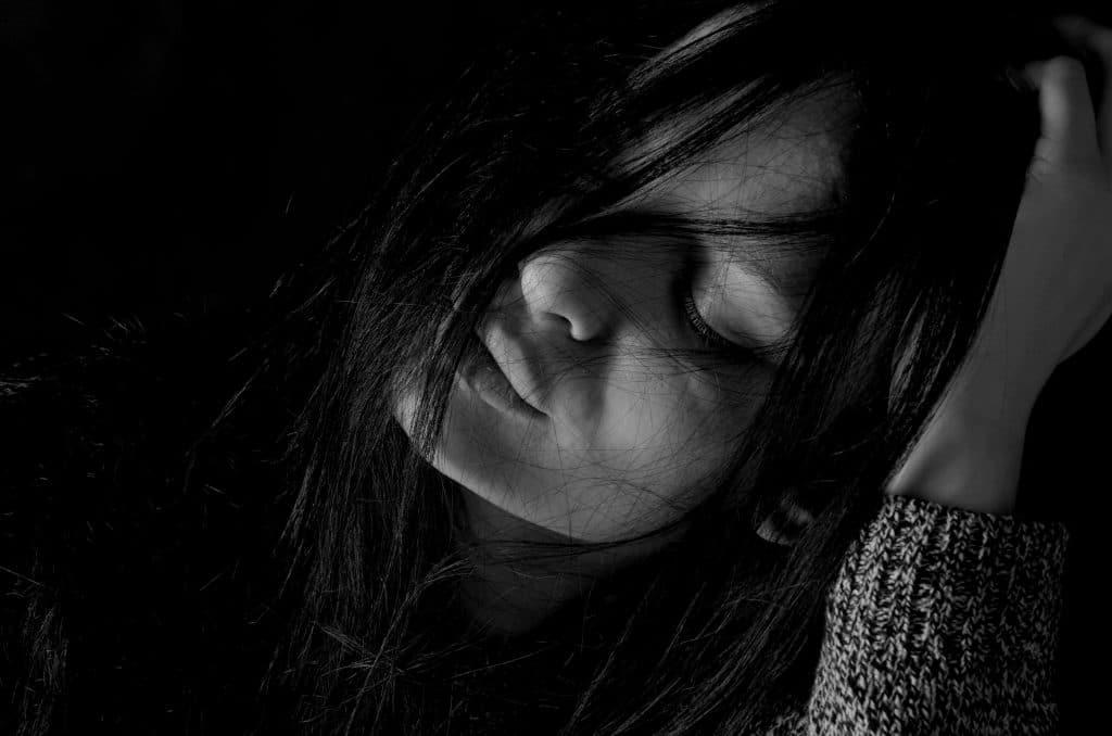 Imagem de uma mulher de cabelos pretos e longos. Ela está com os olhos fechados e deprimida.