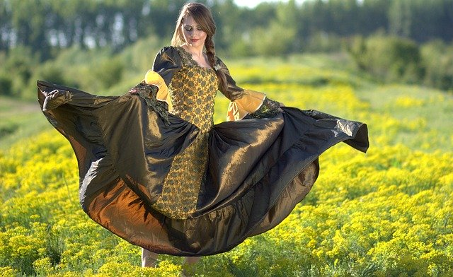 Mulher dançando em grama com vestido de princesa