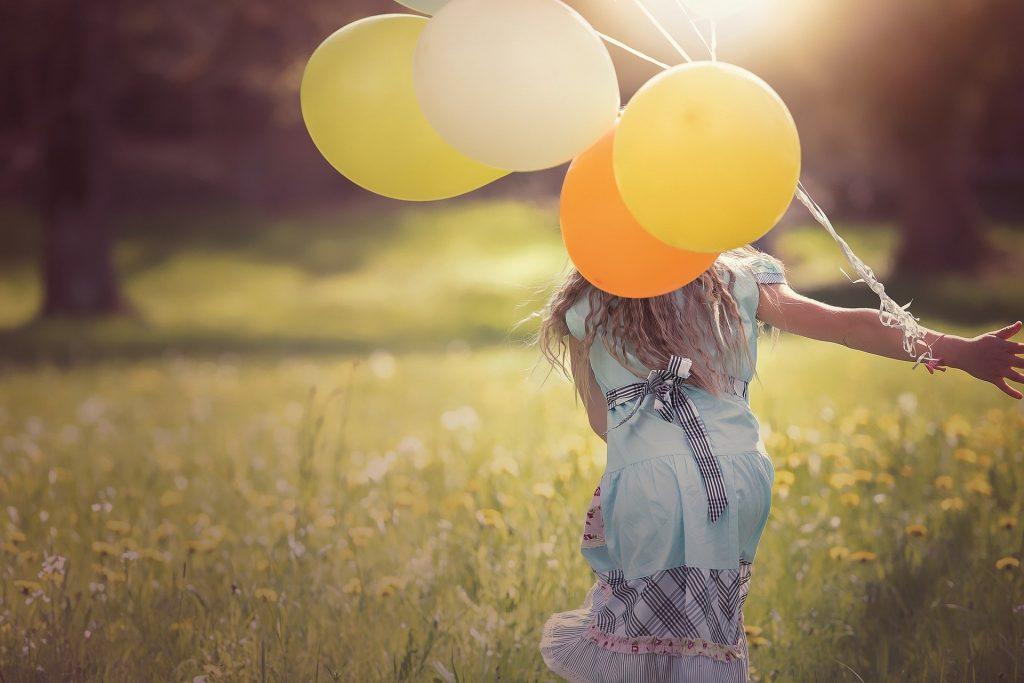 Imagem de uma garota usando um vestido jeans correndo em um campo florido de margaridas. Ela segura em uma das mãos vários balões nas cores amarela, branco e laranja.