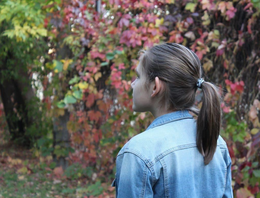 Imagem de uma garota jovem vestindo uma jaqueta jeans azul clara. Ela está em silêncio observando as folhagens que caíram da árvore em uma linda tarde de outono.