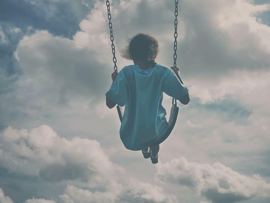 Menina usando vestido tipo camiseta grande, balançando em balanço. Ela está de costas, e bem alto. Ao fundo, o céu com muitas nuvens.