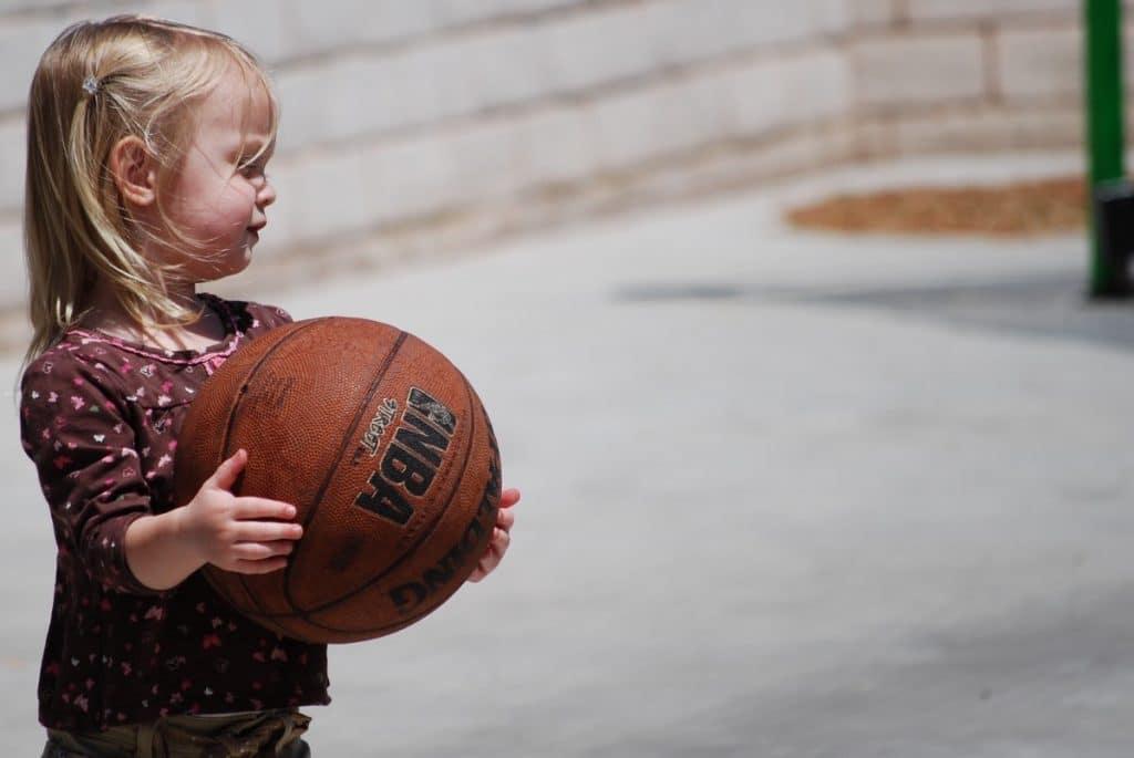 Menina pequena usando blusa comprida e com a franja presa por uma presilha abraçando uma bola de basquete para segurá-la.