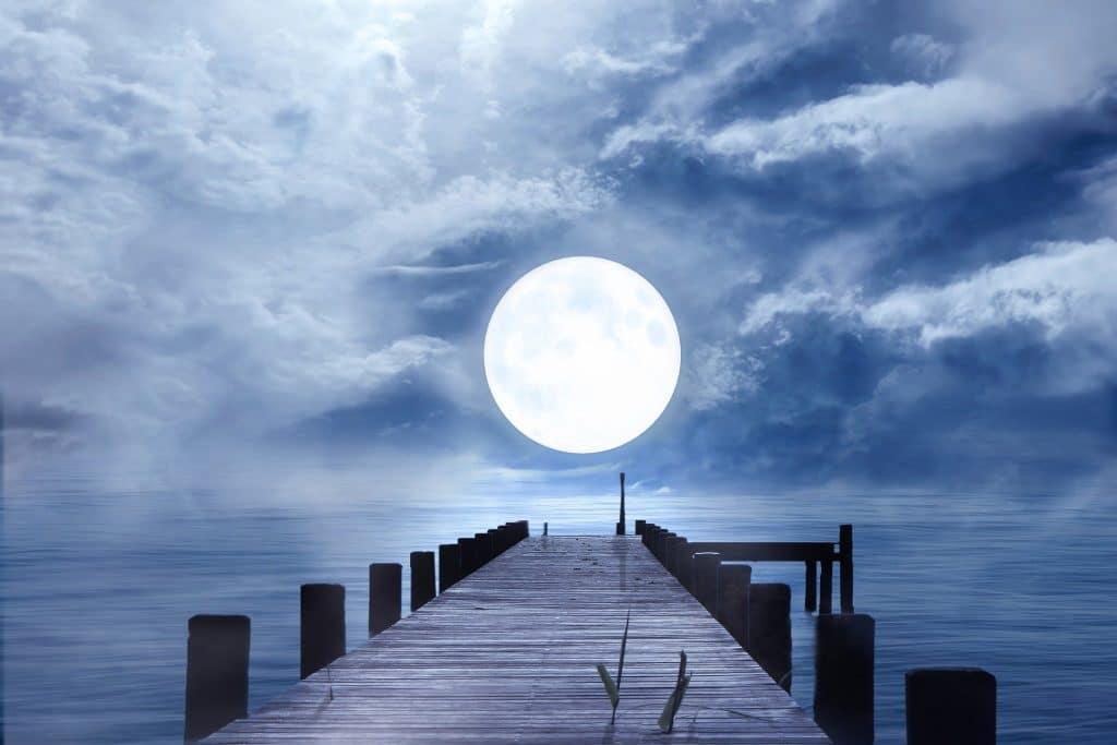Imagem de uma ponte sobre o mar em um início de noite. Ao fundo a lua chei ilumina a paisagem.