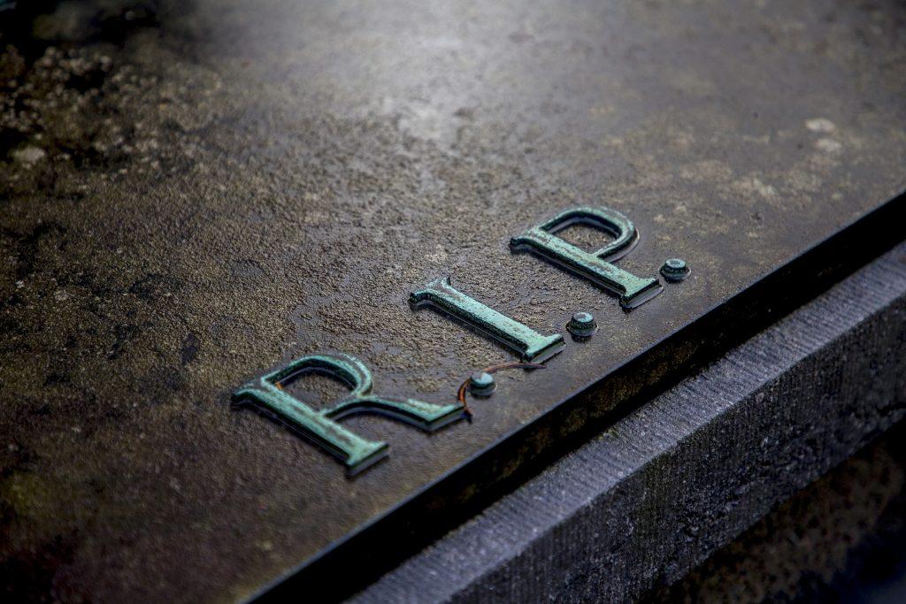 Imagem de uma sepultura dentro do cemitério. Nela está escrito a palavra RIP.