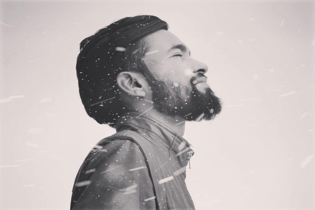 Homem com barba e usando uma faixa no cabelo, com os olhos fechados, de frente para o vento enquanto neva.
