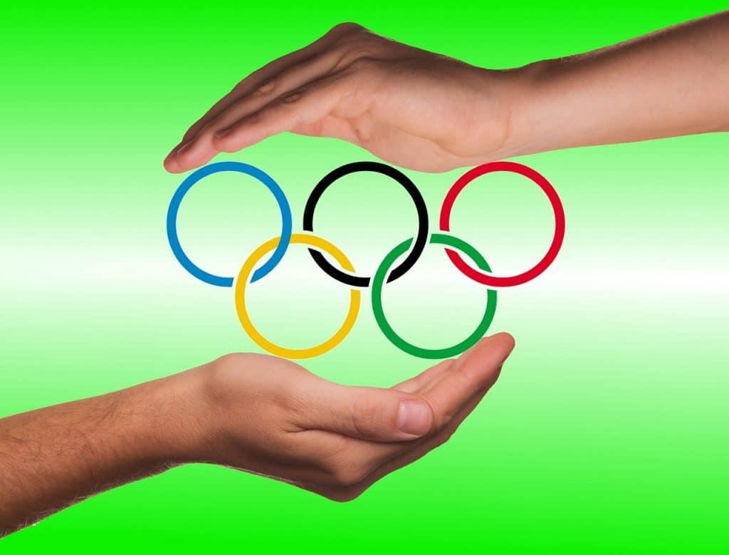 Imagem de duas mãos sobre o símbolo das olimpíadas. Elas estão protegendo os aros coloridos.