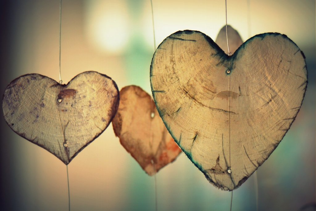 Imagem de três corações pendurados fixdos em um fio de nylon. Os corações são desenhados e moldados em uma folhagem.