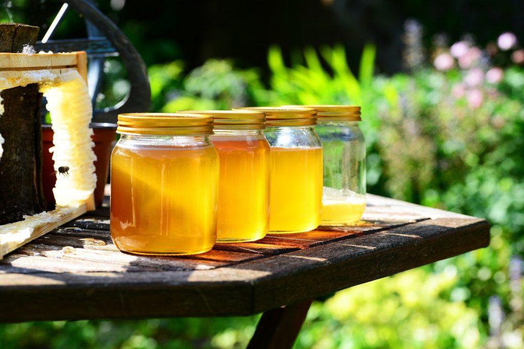 Quatro potes de mel, sendo três cheio e um pote ainda para complementar. Os potes estão sobre a mesa de madeira disposta em um jardim.