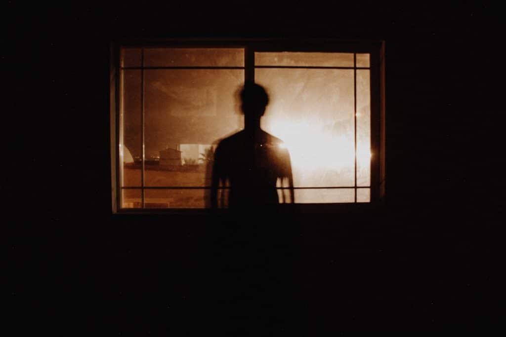 Silhueta de um homem em uma janela. Ao fundo há uma iluminação laranja.