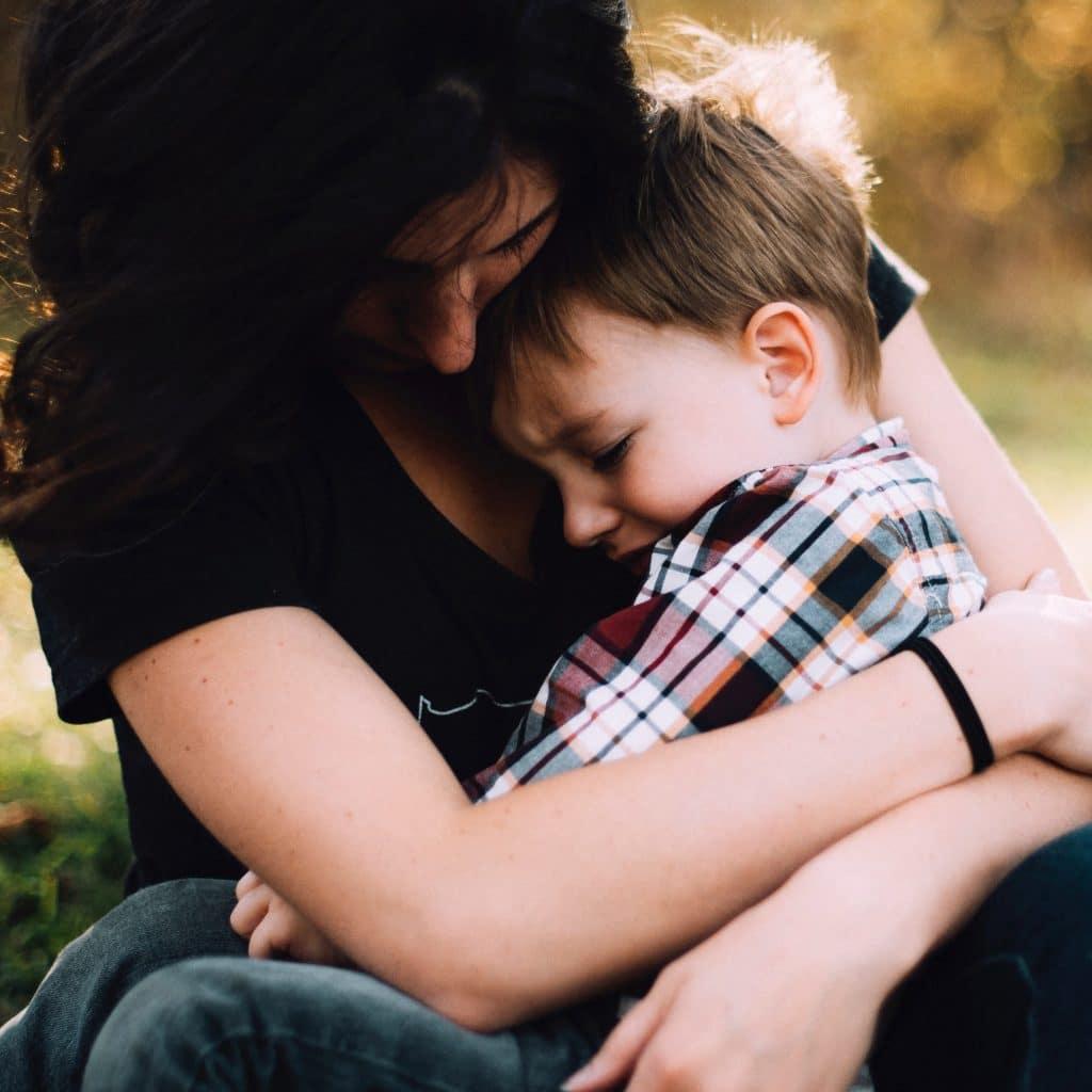Criança triste no colo da mãe