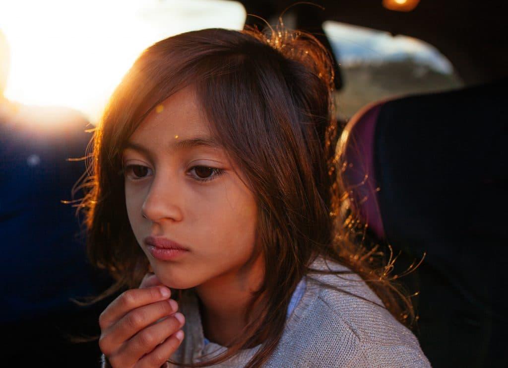 Menina sentada no banco de trás do carro pensando