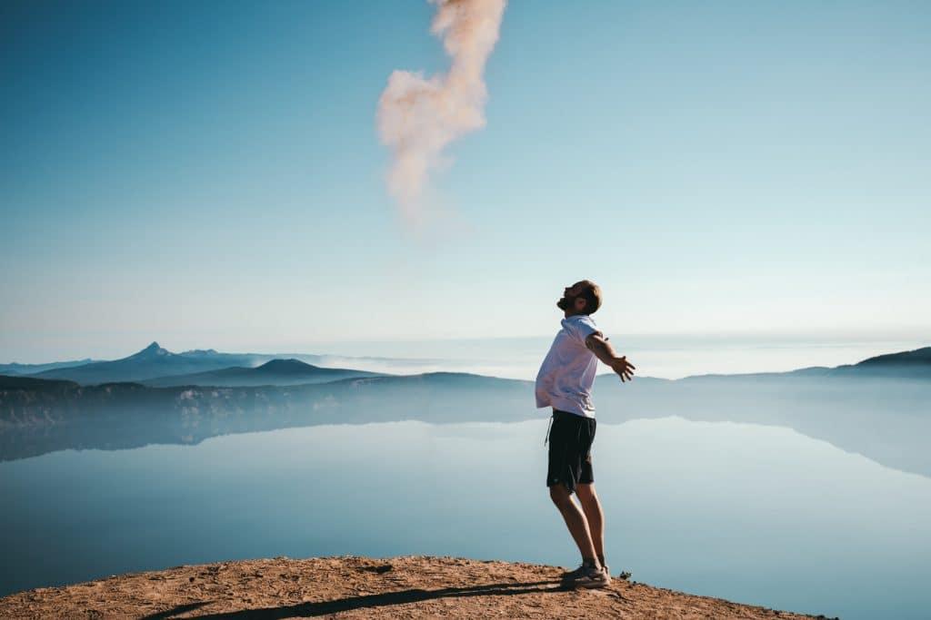Homem em montanha com braços abertos de lado com mar e céu azul ao fundo