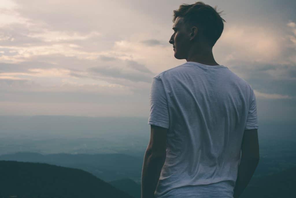 Homem em pé de costas no alto de montanha com céu e paisagem ao fundo