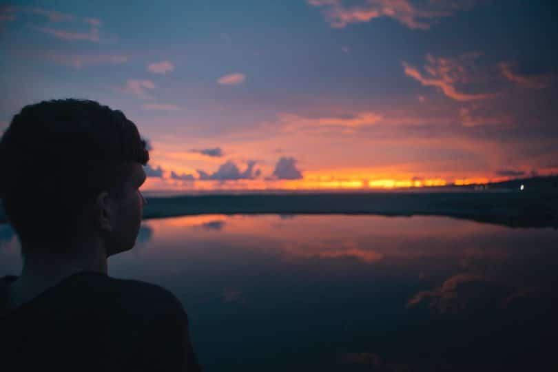 Homem olhando para o por do sol